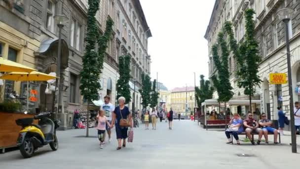 BUDAPEST, HUNGARY - JULY 5, 2018: A young woman is walking with an eight-year-old daughter through the streets of Budapest on a hot summer day. Tourists, vacation.