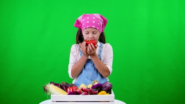 cute, smiling, little farmer girl shows a box with different fresh vegetables, harvest. on green background in studio. Healthy food to your table, Healthy nutrition.