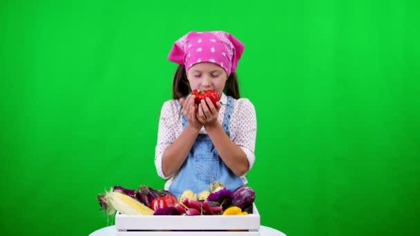 roztomilé, usměvavé, malý farmář dívka ukazuje pole s různými čerstvou zeleninou, sklizeň. na zeleném pozadí ve studiu. Zdravé potraviny na váš stůl, zdravá výživa.