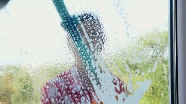 Close-Up Nézd az ablakon, mosolygó kaukázusi gyönyörű nő, kesztyű, takarítás, mosás ablakok mellett különleges mop, egy csomó hab az üveg. Takarítás