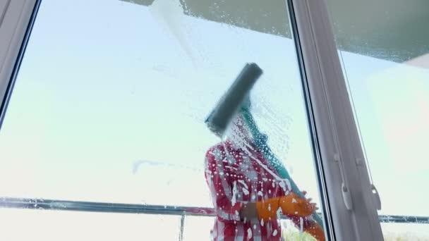 pohled přes okno, usmívající se kavkazské krásná žena, v rukavicích, úklid, mytí oken podle zvláštních mop, se spoustou pěny na sklo. Úklidové služby
