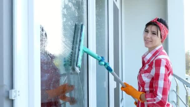 s úsměvem kavkazské krásná žena, Hospodyně nebo veselé ženské pracovník úklidových služeb, v rukavicích, čištění, mytí oken ve speciální mop, se těší její práci. Uklízečka
