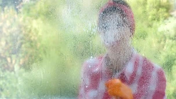 Zobrazit oknem, usmíval se krásná žena v rukavicích, čištění oken čištění ve výrobcích, použitím čisticího prostředku a hadr. pracovník úklidových služeb nebo hospodyňka