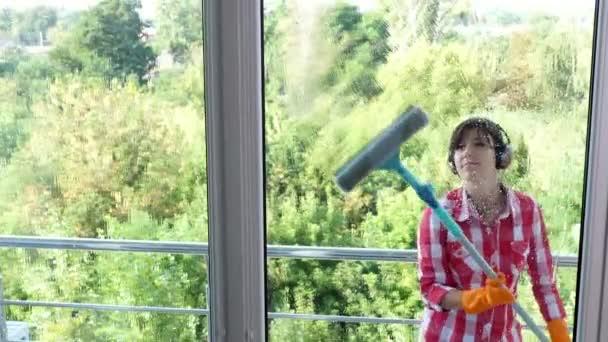 pohled přes okno, usmívající se žena v sluchátka, rukavice, čištění, mytí oken speciální mop, radost z její práce, poslouchat hudbu, čisticí služba pracovníka, Hospodyňka