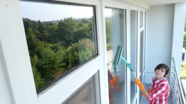 Krásná žena, sluchátka, rukavice, čištění, mytí oken ve speciální mop, radost z její práce, poslouchat hudbu. pracovník úklidových služeb nebo hospodyňka