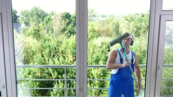 pohled přes okno, pohledný muž pracovník úklidových služeb, v modré kombinéze, se sluchátky, úklid, mytí oken podle zvláštních mop, jeho práci a hudba.