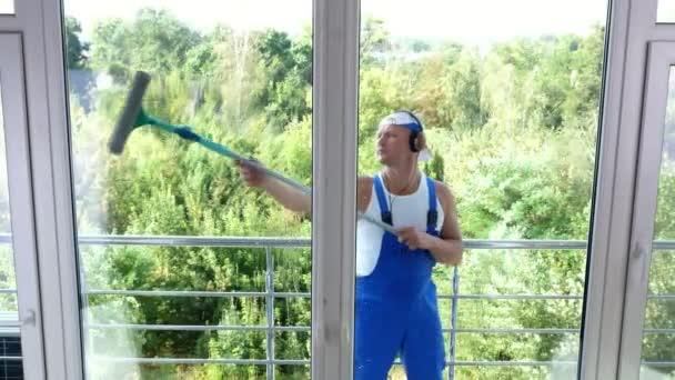Blick aus dem Fenster, gutaussehender männlicher Reinigungsarbeiter, in blauen Overalls, mit Kopfhörern, Fensterputzen, Fensterputzen mit speziellem Wischmopp, Spaß an seiner Arbeit und Musik.