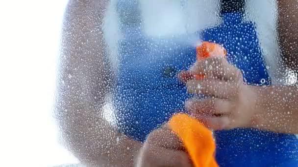 detail, pohled přes okno, mužské čisticí služba pracovníka, v modré kombinéze, čištění oken, úklid ve výrobcích, pracím prostředkem a hadr