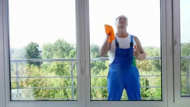 Zobrazit přes okno, atraktivní muž čisticí služba pracovníka, v modré kombinéze a v blaser, čištění oken, úklid ve výrobcích, pomocí saponátu, hadr