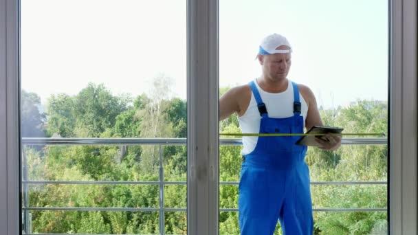 atraktivní stavební dělník dělá měření systému windows pomocí měřicí páska a dělat si poznámky ve formě tablet. okno instalace služby muž
