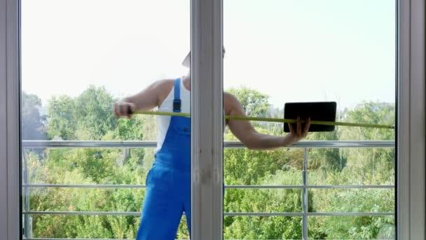 Der attraktive Bauarbeiter misst Fenster mit Maßband und macht sich Notizen in Tablets. Servicekräfte installieren Fenster