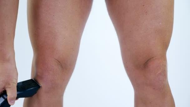 Primer plano de las piernas. un muy peluda hombre corte de pelo pelo del  cuerpo en sus piernas por sí mismo con un cortapelo 835367cd6efe
