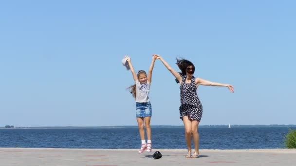 on beach mom and daughter, beautiful brunette in sundress and girl child teenager, dancing, listening to music with mini music bluetooth portable loudspeaker on a hot summer day