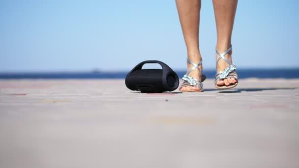 Nahaufnahme, Mini Musik Bluetooth portable schwarz Zylinder Drahtlose Lautsprecher. weibliche Beine in Silber Sandalen mit leuchtend roten Pediküre, Tanzen zur Musik. am Strand, im Sommer