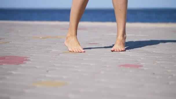na dlažební desky, na pozadí moře zpívají Dámské nohy naboso. horký letní den