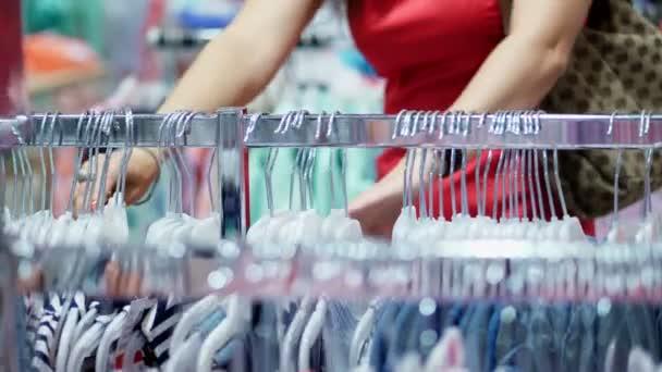 detail, ženské ruce vyřeší mnoho závěsy s oblečení. výběr a nákup oblečení v obchodě. nakupovat. shopaholic. Zákazník při pohledu přes oblečení na regály