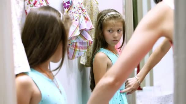nakupovat. v přiléhající místnosti velký obchod, hezká, seriózní dívka, dítě se snaží na nové oblečení, zvolí co koupit. Odraz v zrcadle. dětské konfekce. Dívčí móda.