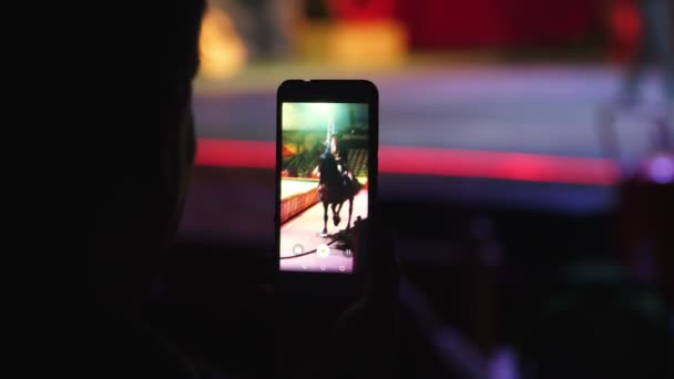 SAFARI PARK POMBIA, ITALY - JULY 7, 2018: in a dark room, the viewer shoots a performance of a pedigree tracked horse on a smartphone. close-up of the gadget.