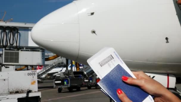 Letiště Boryspil, Ukrajina - 24 října 2018: Detail, Žena ruce držící letenky palubní vstupenku, letenku a pas na letišti, na pozadí letadla