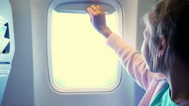 close-up. kid girl lowers the porthole curtain in the airplanes cabin, from there shines a bright light. girl looking out through airplanes window viewing Sky and Clouds and landscape below