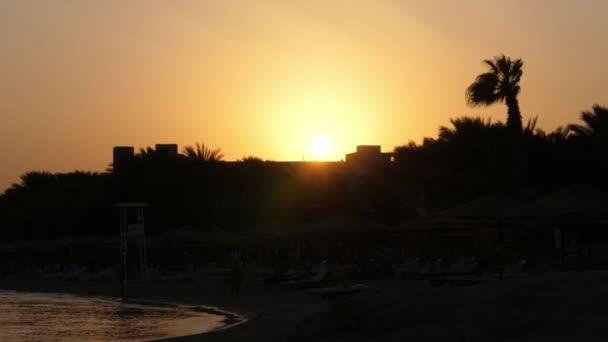 krásná oranžovo červený západ slunce v horké Africe, temné obrysy palem a střechy