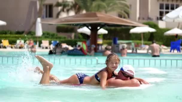 muž v sluneční brýle, otec a dcera, dítě dívka, hrající v bazénové vodě baví spolu. Šťastná rodina relaxaci u bazénu v horkém letním dni ve vodním parku. Letní dovolená koncept