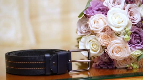 detail, krásné svatební kytice z růží mléčné, bílé a lila. blízko Pánské kožené pás lži. Svatební doplňky
