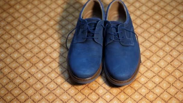 detail, na koberci jsou Pánské módní, stylové modré semišové boty