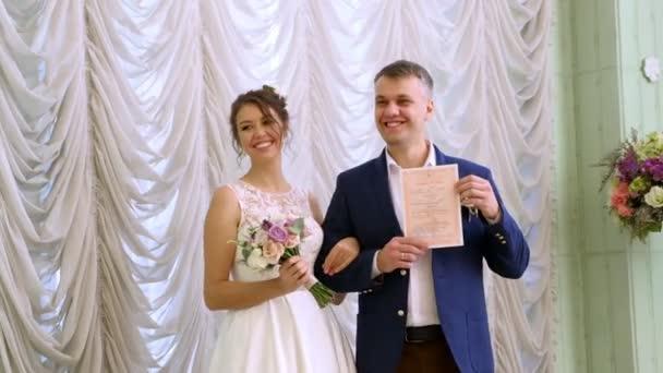 svatební tradice, obřady. svatební obřad. Novomanželé obdrží jejich první rodiny oddací list. Registrace nádherný pár novomanželů