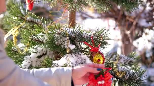 detail, žena zdobí vánoční stromek venku s vánoční ozdoby. Vánoční hračky visí na větvi stromu pokryté sněhem. zimní, mrazivá, zasněžená, slunečný den
