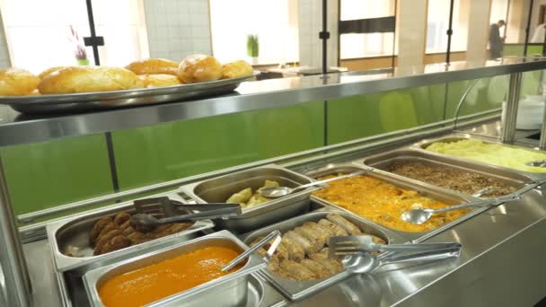 close-up, showcase of Self service restaurant with a variety of dishes, buckwheat porridge, mashed potatoes, vegetable stew with gravy, sausages, mini pizza, pies, sauces