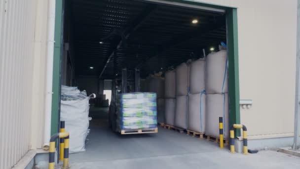 Targonca vezető stacking kukorica nagy csomag raklap a gyűjtő Loader, úgy raklapok el, szállítja őket egy nagy raktár a mezőgazdasági vállalat.