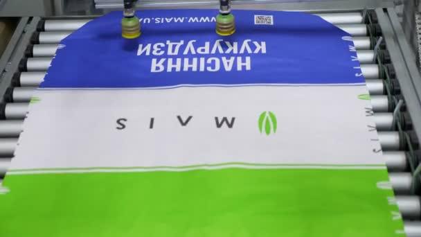 Ukrajina, Cherkasy, 25. března 2019: zemědělská společnost Mais. Zavřete již tištěné balíčky pro zrno, kukuřici, zemědělské produkty na Pásové dopravníkové pásy. tisk, postup v dílně