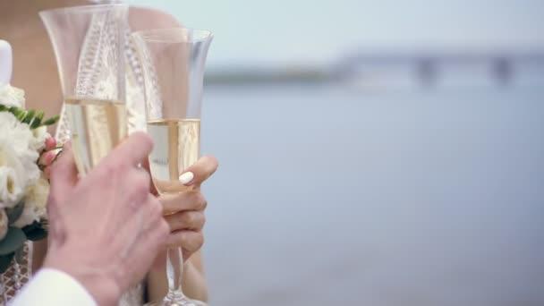 In Großaufnahme halten Frischvermählte Champagnergläser in der Hand. vor dem Hintergrund von blauem Meer und Himmel. Sonniger Frühlingstag. Hochzeit