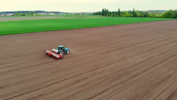 aerial survey, spring, a tractor with special precision planters is working in the field, there is a planting of corn, or sunflower. planting season on the farm. modern technologies in agriculture.