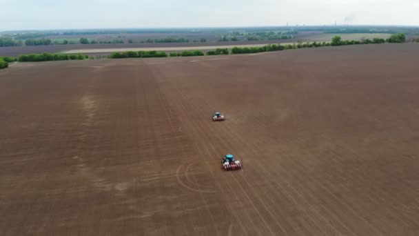 aerial survey, top view, spring, there are two tractors in the field with special precision planters, corn is planted, or sunflower. sowing season on farm. modern technologies in agriculture.