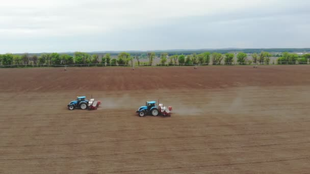 aerial survey, spring, there are two tractors in the field with special precision planters, corn is planted, or sunflower. In field is irrigation system. sowing season on farm. modern technologies in