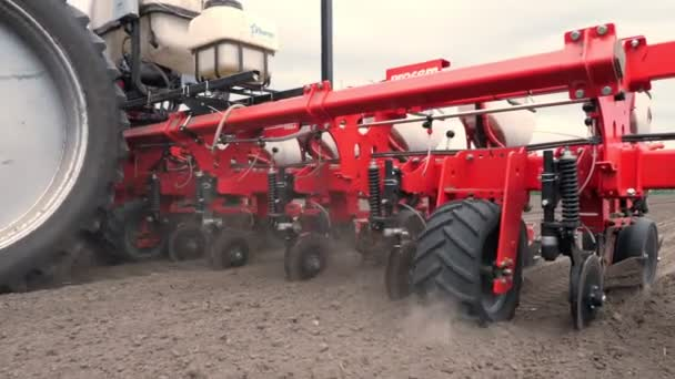 close-up, tractor with special precision planters, seeder is working in the field, agricultural machinery is planting corn, or sunflower seed into freshly plowed land.