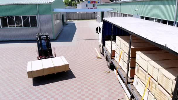 Raktárak. kirakodás a teherautó. áru kirakodása a tehergépkocsból a raktárba. Targonca a forgalomba rakomány teherautó raktár a szabadban