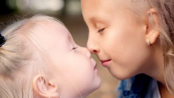 portrét, dvě malé holčičky, dospívající dívka a jedna malá se objímají a něžně si třou své malé nosy.