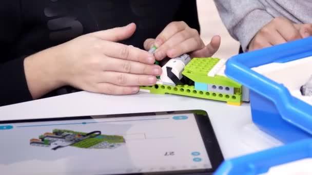 detailní záběr, studenti vytvořit zařízení pomocí designéra, podle výkresů v návodu k použití na tabletu. Robotická škola, Kmenové vzdělávání