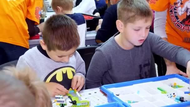žáci, děti, chlapci a dívky, vytvořit zařízení pomocí designera, neželezné části, bloky, podle nákresů v návodu na tablety. Robotická škola, Kmenové vzdělávání.