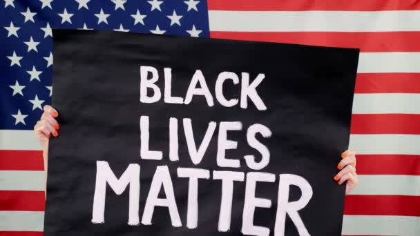 Protester drží na pozadí vlajky USA prapor se sloganem - Black Lives Matter. Boj proti rasismu, za rovná práva v USA.