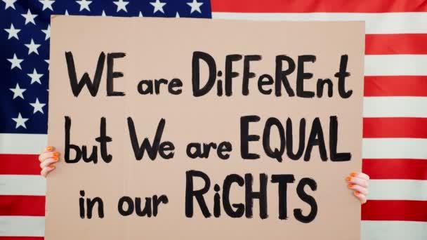 Protester drží prapor se sloganem - my jsme jiní, ale jsme si rovni v našich právech - na pozadí vlajky USA. Boj proti rasismu, za rovná práva v USA.