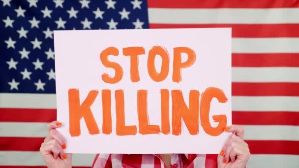 Protester drží prapor se sloganem - Stop kill - na pozadí vlajky USA. Boj proti rasismu, za rovná práva v USA.