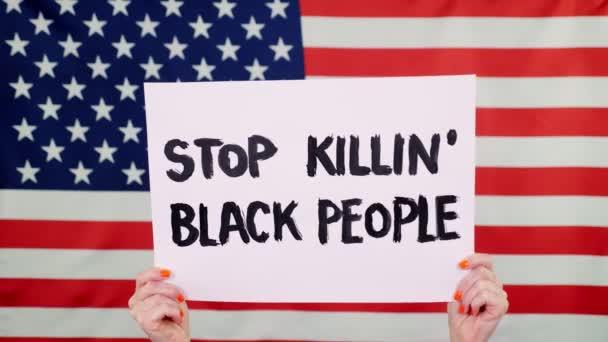 Protester drží prapor s heslem - Přestaňte zabíjet Černé lidi - na pozadí vlajky USA. Boj proti rasismu, za rovná práva v USA.