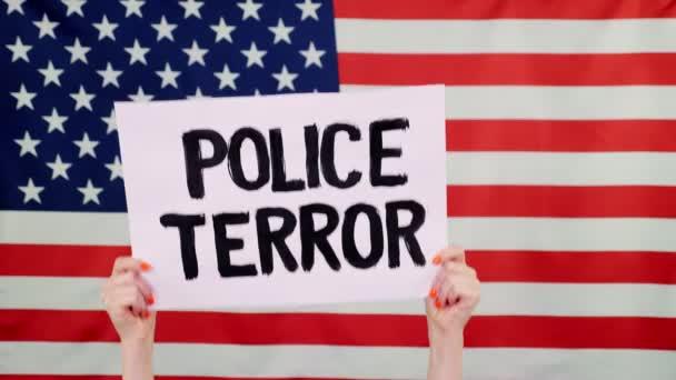 Protester drží na pozadí vlajky USA prapor se sloganem - Policejní teror. Boj proti rasismu, za rovná práva v USA.