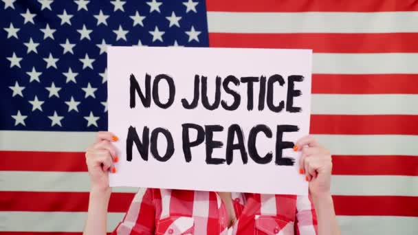 Protester drží prapor se sloganem - NE SPRAVEDLNOST NO PEACE - na pozadí vlajky USA. Boj proti rasismu, za rovná práva v USA.