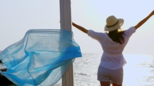 junge Frau in Sommerkleidung und Sonnenhut, trifft die Morgendämmerung am Strand am Meer. Nahaufnahme ihres Gepäcks mit medizinischer Maske. Sommerurlaub nach Coronavirus-Ausbruch beendet.
