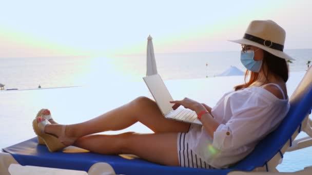 junge Frau in Schutzmaske, Sonnenhut und Sommerkleidung, am Laptop sitzend auf einer Sonnenliege am Pool. Arbeit aus der Ferne. Neue Normalität. Leben nach Covid19.